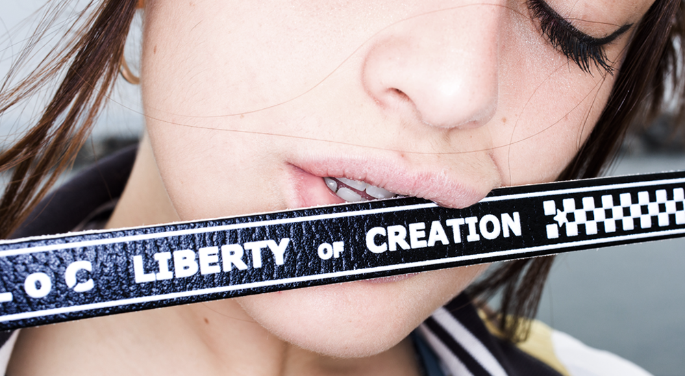 ragazza morde una tracolla della borsa pollicina di liberty of creation in vera pelle con stampa digitale 3d bianca e nera reversibile